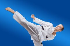Sul fondo del blu un atleta batte la scossa del roundhouse Fotografia Stock