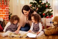 Sul giorno di Natale la mie madre e seduta gemellata di due piccola figlie immagine stock libera da diritti