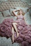 Sul grande letto è la ragazza in un vestito magnifico Fotografia Stock
