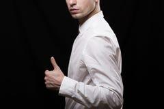 Sul nero un fondo ha girato il giovane obliquo in una camicia bianca Immagini Stock