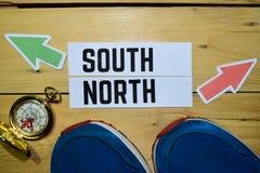 Sul ou norte oposto aos sinais de sentido com sapatilhas e compasso no fundo de madeira do vintage foto de stock