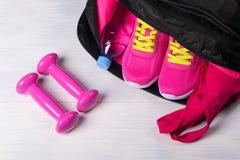 Sul pavimento di legno mette in mostra la borsa con le cose rosa in ha scoperto e due teste di legno immagini stock