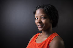 Sul - professor africano ou afro-americano da mulher no fundo da placa do preto do giz Foto de Stock