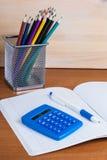 Sul quaderno in un calcolatore ed in una penna blu di menzogne delle cellule Immagine Stock