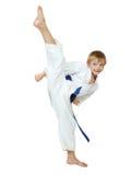 Sul ragazzo bianco del fondo un atleta in un kimono esegue una circolare della gamba di scossa isolata Immagine Stock Libera da Diritti