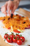 Sul ramo della priorità alta di piccoli pomodori ciliegia Mano con oliva nera su fondo vago Fotografia Stock
