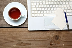 Sul tè d'annata, sul computer portatile e sui biglietti da visita della tavola Immagine Stock Libera da Diritti