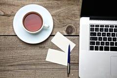 Sul tè d'annata, sul computer portatile e sui biglietti da visita della tavola Immagine Stock