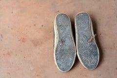 sular av gamla sportskor på smutsig cementjordning Arkivfoto