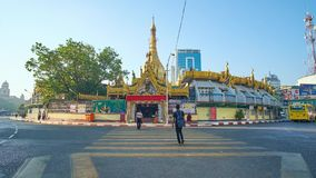 Sule Pagoda in Yangon Downtown, Myanmar. YANGON, MYANMAR - FEBRUARY 14, 2018: Morning activity in Downtown, numerous pedestrians on crossing on the roundabout at stock footage