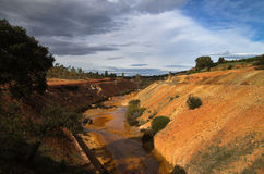 Sulfur and iron polluted river amongst gravel and scoria fields Stock Photos