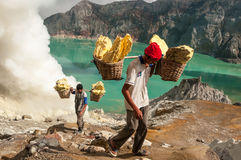 Sulfur at Kawah Ijen. Kawah Ijen, Indonesia - April 24,2010 : Worker carries sulfur inside Ijen crater in Ijen Volcano, Indonesia. He carries the load of around royalty free stock photo
