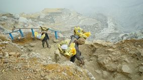 Sulfur miner. These two people earns a living as traditional sulfur miner in mount Ijen royalty free stock image