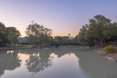 Sulfur. Pond of Rotorua at sunset. At the far end of the pond is an arching walking bridge with trees in the backdrop. The pond has a high  content from an royalty free stock photo