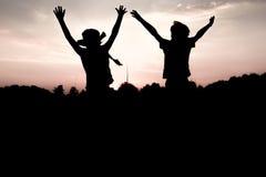 Sulhouettes av barn som hoppar av en kulle på solnedgången Royaltyfri Foto