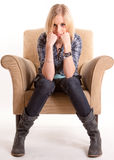 Sulking girl on an armchair Royalty Free Stock Photo