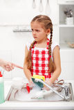 Sulking little girl doing the dishes Stock Images