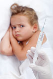 Sulking little girl receiving injection Stock Photo
