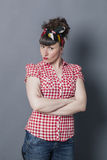 Sulking retro woman crossing her arms to express her disagreement. Sulking brunette woman with retro hairstyle and fifties look crossing her arms to express her Stock Photo