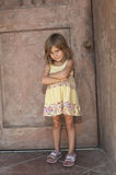 Sulking toddler. Sulky female toddler with arms folded, door in background Royalty Free Stock Image