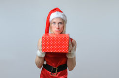 Sulking woman holding a Christmas gift. Royalty Free Stock Photography