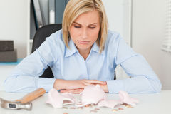 Sulking woman sitting in front. Sulking woman sitting inher office in front of an shattered piggy bank with less in than expected Royalty Free Stock Photos