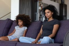 Sulky african child and mother sitting on sofa not talking. Unhappy sulky african child girl and annoyed mother sitting on sofa not talking after fight, stubborn royalty free stock image