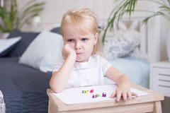 Sulky grumpy attractive little blond girl. Sitting with paper and crayons at a small wooden desk staring off to the side with her chin on her hand Stock Image