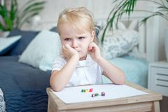 Sulky grumpy attractive little blond girl. Sitting with paper and crayons at a small wooden desk staring off to the side with her chin on her hand Royalty Free Stock Photo