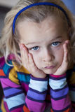 Sulky little girl with head in hands. Portrait of child, grumpy and pouting stock photography