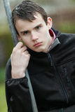 Sulky teenage boy glowering at the camera. Sulky teenage boy with damp hair from the misty weather leaning on a pole glowering at the camera with pouting lips Royalty Free Stock Images