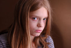 Sulky young girl. Portrait of long haired young girl with sulky expression, dark background Stock Photo