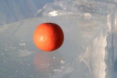 Sull'orlo di ghiaccio la tavola si trova arancio arancio riscalda nel freddo, nell'inverno e nel ghiaccio Fotografie Stock Libere da Diritti