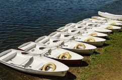 Sulla banchina, le imbarcazioni a remi attraccano in una fila, in ogni bagnino e pagaie immagine stock libera da diritti