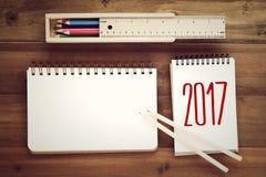 2017 sulla carta, sul contenitore e sulla matita di taccuino sul fondo della tavola con Immagini Stock