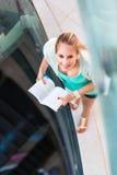 Sulla città universitaria - abbastanza, studentessa con i libri Immagine Stock