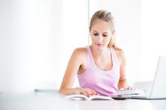 Sulla città universitaria - abbastanza, studentessa con i libri ed il funzionamento del computer portatile Fotografie Stock