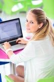 Sulla città universitaria - abbastanza, sulla studentessa con i libri e sul computer portatile Fotografia Stock