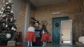 Sulla notte di Natale due le ragazze incontrano felicemente il loro padre che tiene i regali per loro Famiglia felice Nuovo anno archivi video