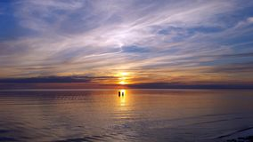 Sulla riflessione del sole nel mare, le siluette della gente sono visibili, durante il tramonto magnifico di colore che riflette  Fotografie Stock