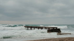 Sulla riva, battito delle onde sul pilastro sulla riva durante la tempesta video d archivio