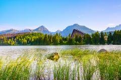 Sulla riva del lago con alta erba là è visto una casa affascinante Fotografia Stock Libera da Diritti