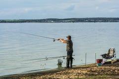Sulla riva del lago, un uomo sta pescando con una canna da pesca Fotografia Stock Libera da Diritti