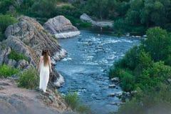 Sulla scogliera sta una bella ragazza in un vestito bianco con i dreadlocks Contro il contesto del fiume veloce e turbolento fotografia stock libera da diritti