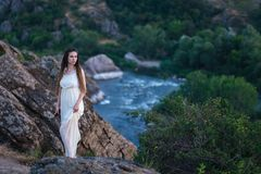 Sulla scogliera sta una bella ragazza in un vestito bianco con i dreadlocks Contro il contesto del fiume veloce e turbolento immagini stock libere da diritti