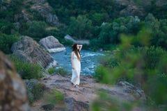 Sulla scogliera sta una bella ragazza in un vestito bianco con i dreadlocks Contro il contesto del fiume veloce e turbolento fotografie stock libere da diritti