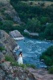 Sulla scogliera sta una bella ragazza in un vestito bianco con i dreadlocks Contro il contesto del fiume veloce e turbolento immagini stock