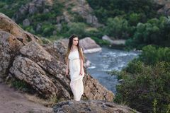 Sulla scogliera sta una bella ragazza in un vestito bianco con i dreadlocks Contro il contesto del fiume veloce e turbolento immagine stock libera da diritti