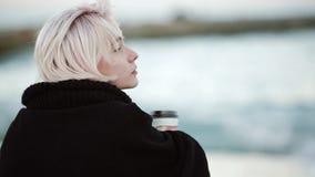 Sulla spiaggia, beve il caffè Esamina la distanza, raddrizza i suoi capelli Vista dalla parte posteriore stock footage