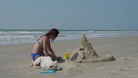 Sulla spiaggia, la ragazza sta costruendo un castello della sabbia Rilassi sulla spiaggia ricorso 4K stock footage